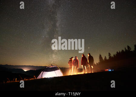 Night summer camping in the mountains. Back view of happy friends hikers having a rest together around campfire near glowing tourist tent under amazin - Stock Photo