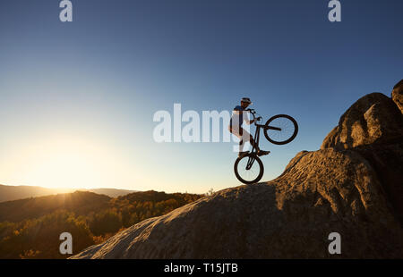 Silhouette of courageous cyclist balancing on back wheel on trial bicycle. Professional sportsman biker making acrobatic stunt on the top of mountain  - Stock Photo