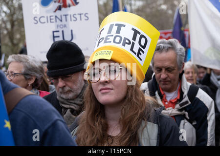 London, UK. 23rd Mar, 2019. Woman in crowd wearing Put it to the People yellow hat at protest march. London 23 March 2019 Credit: Chris Moos/Alamy Live News - Stock Photo