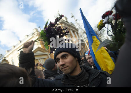 Kyiv, Kyiv Oblast, Ukraine. 23rd Mar, 2019. A protester seen throwing bouquets of plastic flowers at police in riot gear outside of the Presidential Administration Building during the demonstration. Protesters gathered in Maidan Square then marched to the Presidential Administration building to call on President Petro Poroshenko to bring corrupt governmental officials to justice. With the Ukrainian Elections being held at the end of March the political tensions run very high. Credit: Matthew Hatcher/SOPA Images/ZUMA Wire/Alamy Live News - Stock Photo