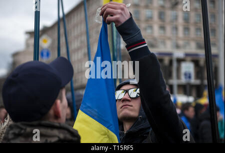 Kyiv, Kyiv Oblast, Ukraine. 23rd Mar, 2019. A protester seen with a flag during the demonstration. Protesters gathered in Maidan Square then marched to the Presidential Administration building to call on President Petro Poroshenko to bring corrupt governmental officials to justice. With the Ukrainian Elections being held at the end of March the political tensions run very high. Credit: Matthew Hatcher/SOPA Images/ZUMA Wire/Alamy Live News - Stock Photo