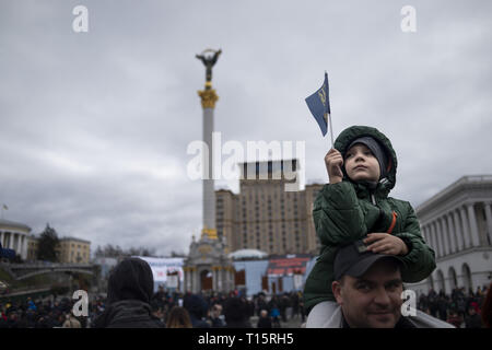 Kyiv, Kyiv Oblast, Ukraine. 23rd Mar, 2019. A boy seen waving a flag as he watches on during the demonstration. Protesters gathered in Maidan Square then marched to the Presidential Administration building to call on President Petro Poroshenko to bring corrupt governmental officials to justice. With the Ukrainian Elections being held at the end of March the political tensions run very high. Credit: Matthew Hatcher/SOPA Images/ZUMA Wire/Alamy Live News - Stock Photo