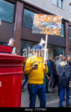 London, UK. 23rd Mar 2019.  Over a million people march for the People's Vote, for a second referendum on Brexit, man holding a Revoke This Joke sign Credit: Nathaniel Noir/Alamy Live News - Stock Photo