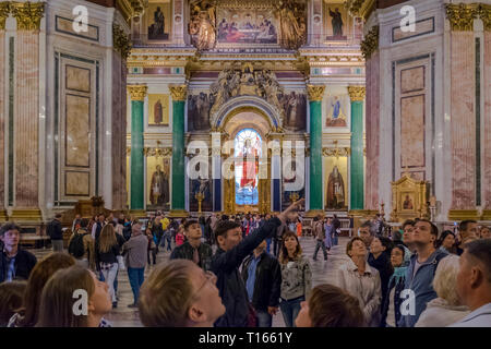 Tourists gazing at the giant interior of Saint Isaac's Cathedral in St. Petersburg, Russia. - Stock Photo