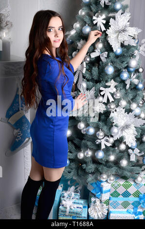 Young girl in a blue dress dresses up Christmas tree. Girl in formal attire catches spherical shiny toy on the Christmas tree. The process preparing f - Stock Photo