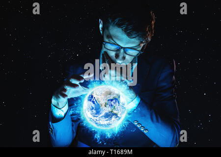 A man businessman holding hands over a blue glowing sphere in the form of planet earth. Elements furnished by NASA - Stock Photo