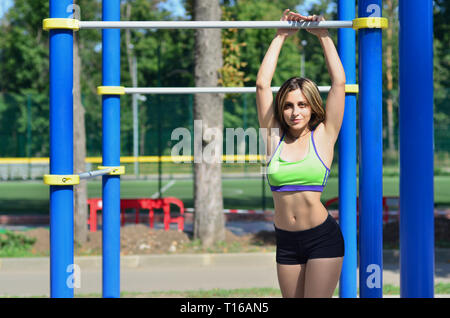 Young caucasian female in a bright green sportswear leaned against the horizontal bar on the sports field or playground. Photo of an athlete girl with - Stock Photo