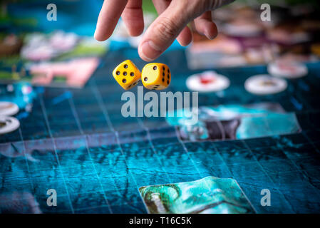 The hand throws two yellow dice on the blue field of the fantasy game. Gaming moments in dynamics. Luck and excitement. Concept Board games strategy - Stock Photo