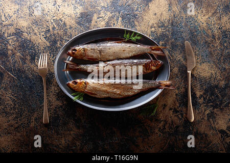 Smoked Baltic herring with dill on a black background. Copy space for your text. Top view. - Stock Photo