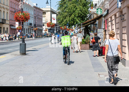 Warsaw, Poland - August 23, 2018: Uber eats bicycle man with green bag in old town historic street in capital city during sunny summer day called Krak - Stock Photo