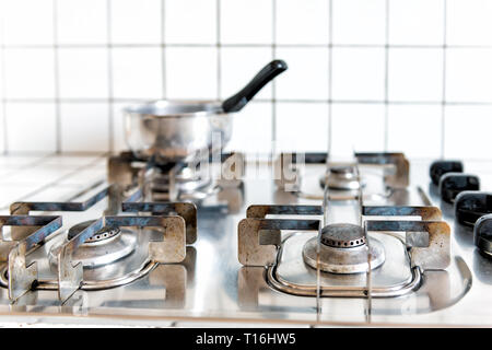 Closeup of vintage retro tiled gas stove top with tiles white countertop and stainless steel pot cooking in kitchen - Stock Photo