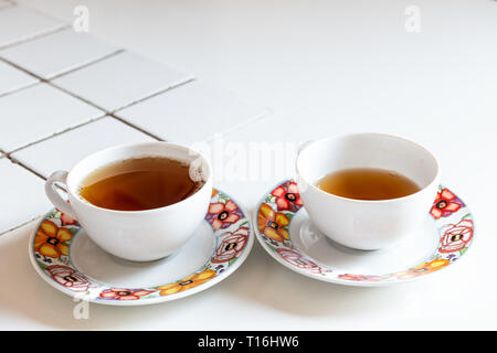 Two teacups closeup with black or herbal tea on white tiled table in Italian villa rustic Tuscany home kitchen sunlight during morning breakfast - Stock Photo