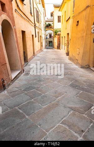 Chiusi, Italy empty road in small town village in Tuscany narrow vertical view during day with orange yellow bright vibrant vivid color walls closeup  - Stock Photo