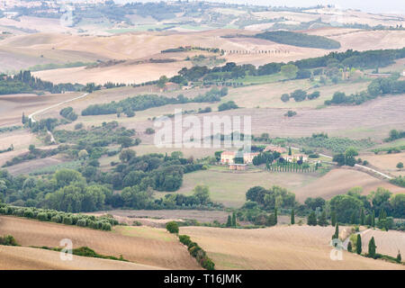 Autumn countryside in Val D'Orcia Tuscany, Italy with rolling plowed brown hills and villas with farm landscape idyllic meadow fields high angle - Stock Photo