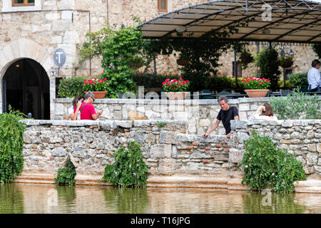 Bagno Vignoni, Italy - August 26, 2018: Medieval town by San Quirico d'Orcia in Val d'Orcia, Tuscany with people tourists looking at pool - Stock Photo