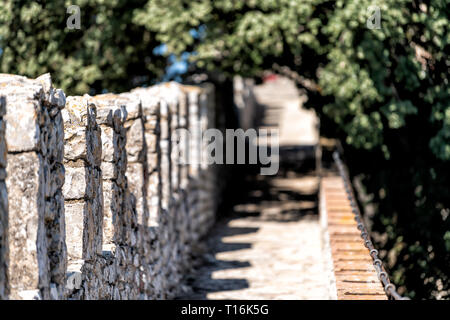 Castiglione del Lago medieval fortress fort wall railing in Umbria, Italy and Rocca with Medievale o Rocca del Leone tower trees in sunny summer day - Stock Photo