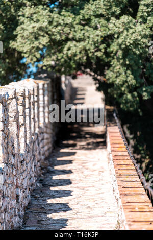 Castiglione del Lago medieval fortress fort wall in Umbria, Italy and Rocca with Medievale o Rocca del Leone tower trees in sunny summer day - Stock Photo