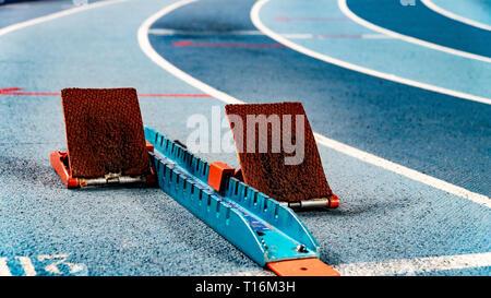Athletics starting blocks on race blue track - Stock Photo