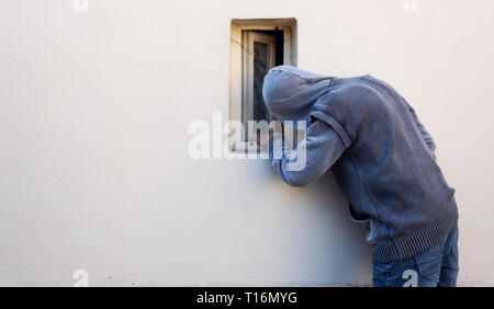 Burglar or thief or robber is looking through the small window and with plan to steal something - Stock Photo