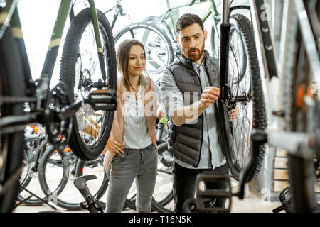 Salesman helping young woman to choose a new bicycle to buy standing in the bicycle shop - Stock Photo