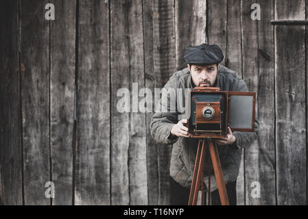Photographer prepares for shooting on large format camera. Concept - photography of the 1930s-1950s, matte effect - Stock Photo