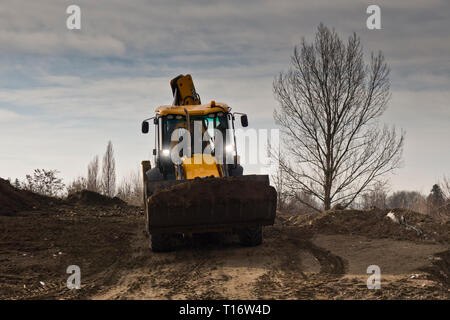 excavator moving terrain in a construction site - Stock Photo