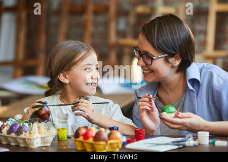 Little Girl Painting Easter Eggs with Mom - Stock Photo