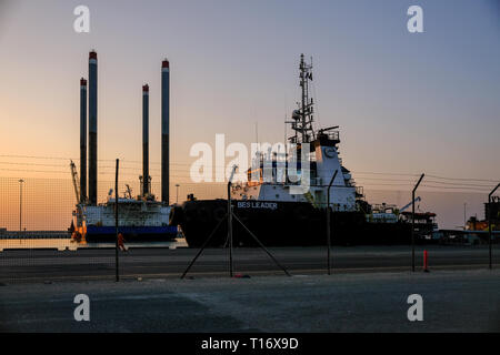 December 29, 2018 - Abu Dhabi, UAE:  Evening view of Zayed Port with docked ships and oil rigs - Stock Photo