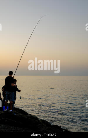 December 29, 2018 - Abu Dhabi, UAE: Silhouette of a man fishing with a fishing rod at evening - Stock Photo