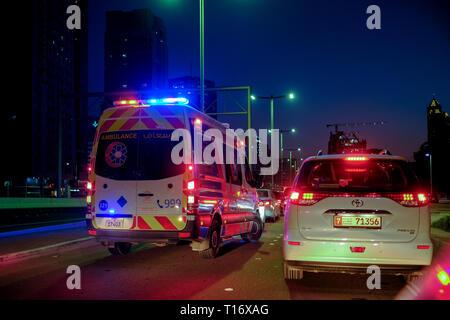 December 29, 2018 - Abu Dhabi, UAE: Ambulance crossing another vehicle with full speed while Flashing hazard lights - Stock Photo
