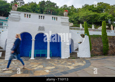 Cerulean and white seashore pavilion and blur image of a woman walking by, Portmeirion, Gwynedd, North Wales, United Kingdom - Stock Photo