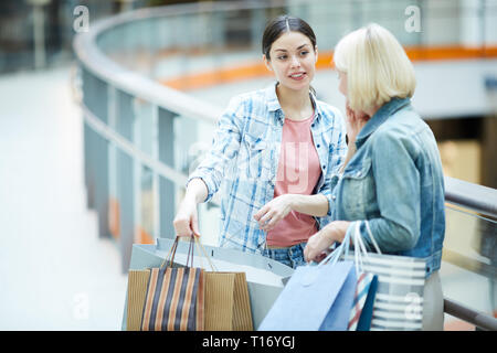 Showing off new dress in shopping bag - Stock Photo