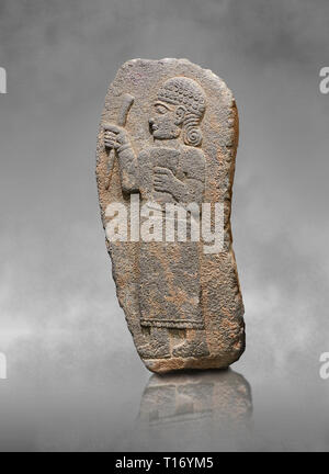 Hittite monumental relief sculpture of a figure holding a document. Adana Archaeology Museum, Turkey. Against a grey art background - Stock Photo