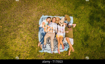 Top vertical aerial view of group of friends lay down on the meadow and enjoy the friendship playing a guitar and relaxing all together - people  frie - Stock Photo