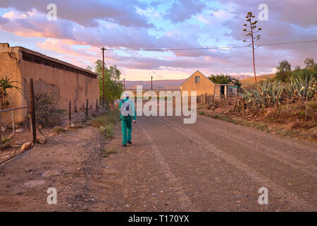 Karoo dirt road leading to a bend in morning light. Man in green overall by farm house seen from back walking to work - Stock Photo