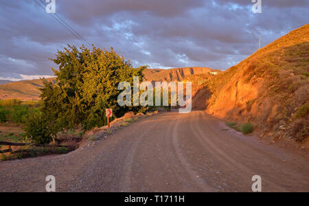 Karoo dirt road leading to a bend in morning light. - Stock Photo