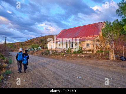 Karoo dirt road leading to a bend in morning light. Two teenagers  seen from back walking to school, passing ancient farm house - Stock Photo