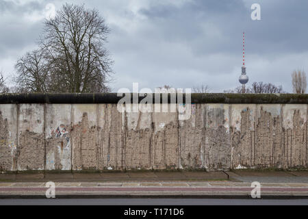 Front view of a section of the original Berlin Wall at the Berlin Wall Memorial (Berliner Mauer) in Berlin. Fernsehturm TV Tower is in the background. - Stock Photo