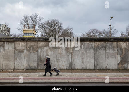 Old woman walking in front view of the original Berlin Wall and watchtower at the Berlin Wall Memorial (Berliner Mauer) in Berlin, Germany. - Stock Photo