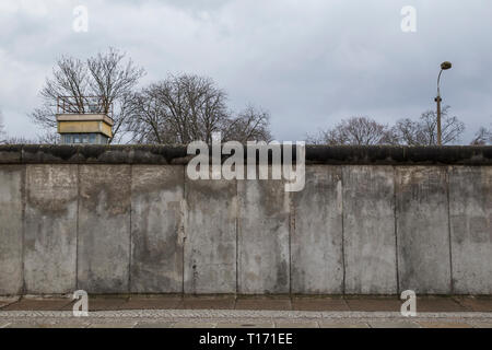 Front view of a section of the original Berlin Wall and watchtower at the Berlin Wall Memorial (Berliner Mauer) in Berlin, Germany, on a cloudy day. - Stock Photo
