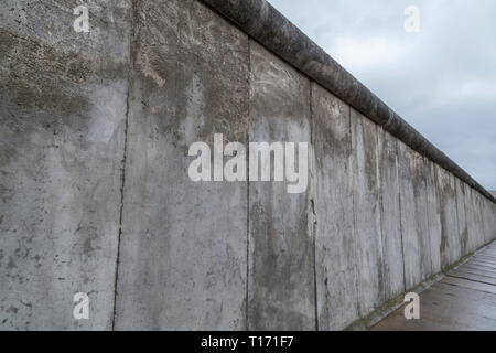 Side view of a section of the original Berlin Wall at the Berlin Wall Memorial (Berliner Mauer) in Berlin, Germany, on a cloudy day. - Stock Photo