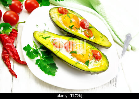 Scrambled eggs with cherry tomatoes in two halves of avocado in a plate, towel and fork on white wooden board background - Stock Photo