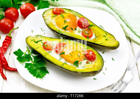 Scrambled eggs with cherry tomatoes in two halves of avocado in a plate, kitchen towel and fork on the background of wooden boards - Stock Photo