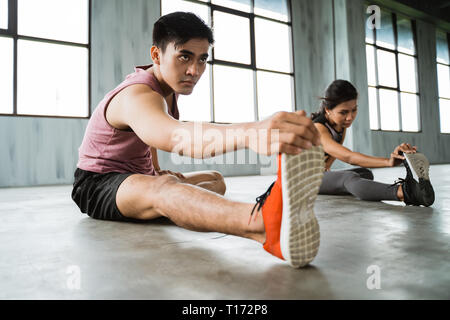 asian young man doing legs stretching before core exercise - Stock Photo
