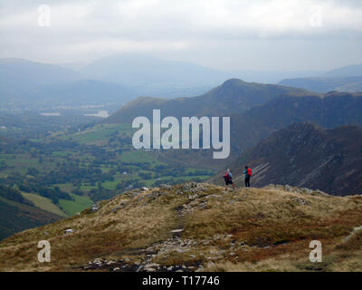 Two Hikers Looking down the Newlands Valley Towards Cat Bells from the Wainwright Robinson in the Lake District National Park, Cumbria, UK. - Stock Photo