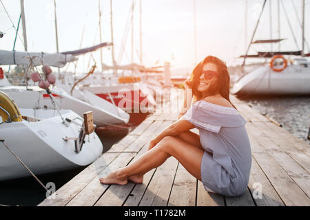 Gorgeous model sits on pier and smiling. She poses. Young woman keeps legs together and holds hair with hand from waving. She looks happy. - Stock Photo