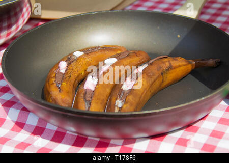 Fried bananas in a skillet. Unusual fruit dishes - Stock Photo