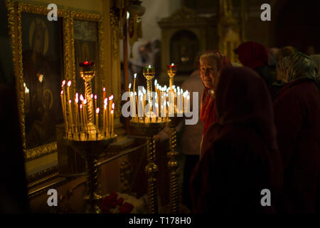 Belarus, Gomel, April 30, 2016. Nikolsky monastery.The celebration of Orthodox Easter. A woman in the church lights a candle. - Stock Photo
