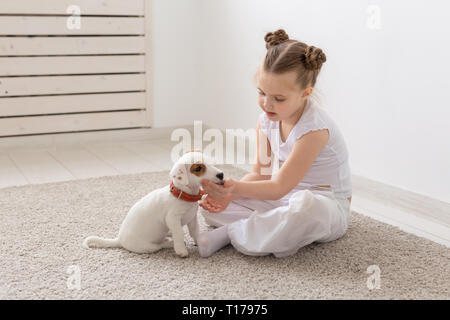 people, children and pets concept - little child girl sitting on the floor with cute puppy Jack Russell Terrier and playing - Stock Photo