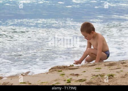 Little boy playing with sand near the sea. Child on vacation at the resort - Stock Photo